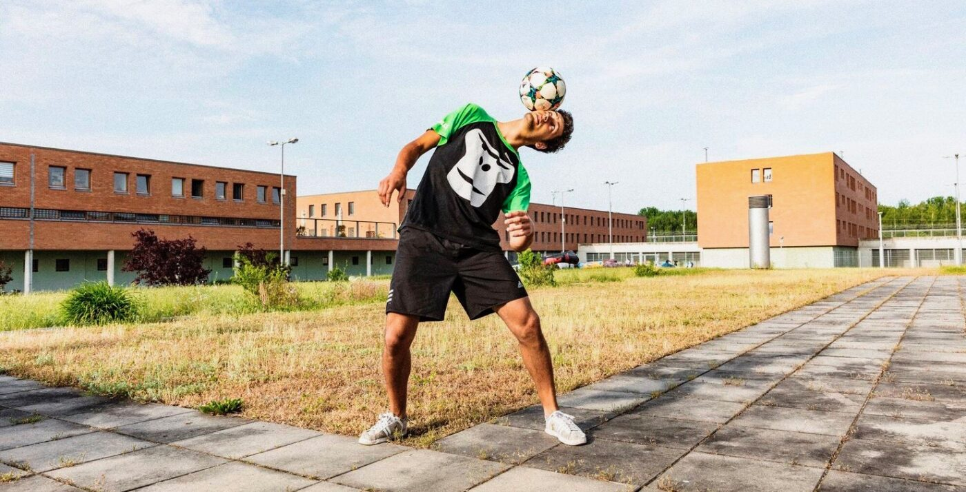 GORILLA Botschafter jongliert einen Fußball auf dem Kopf.