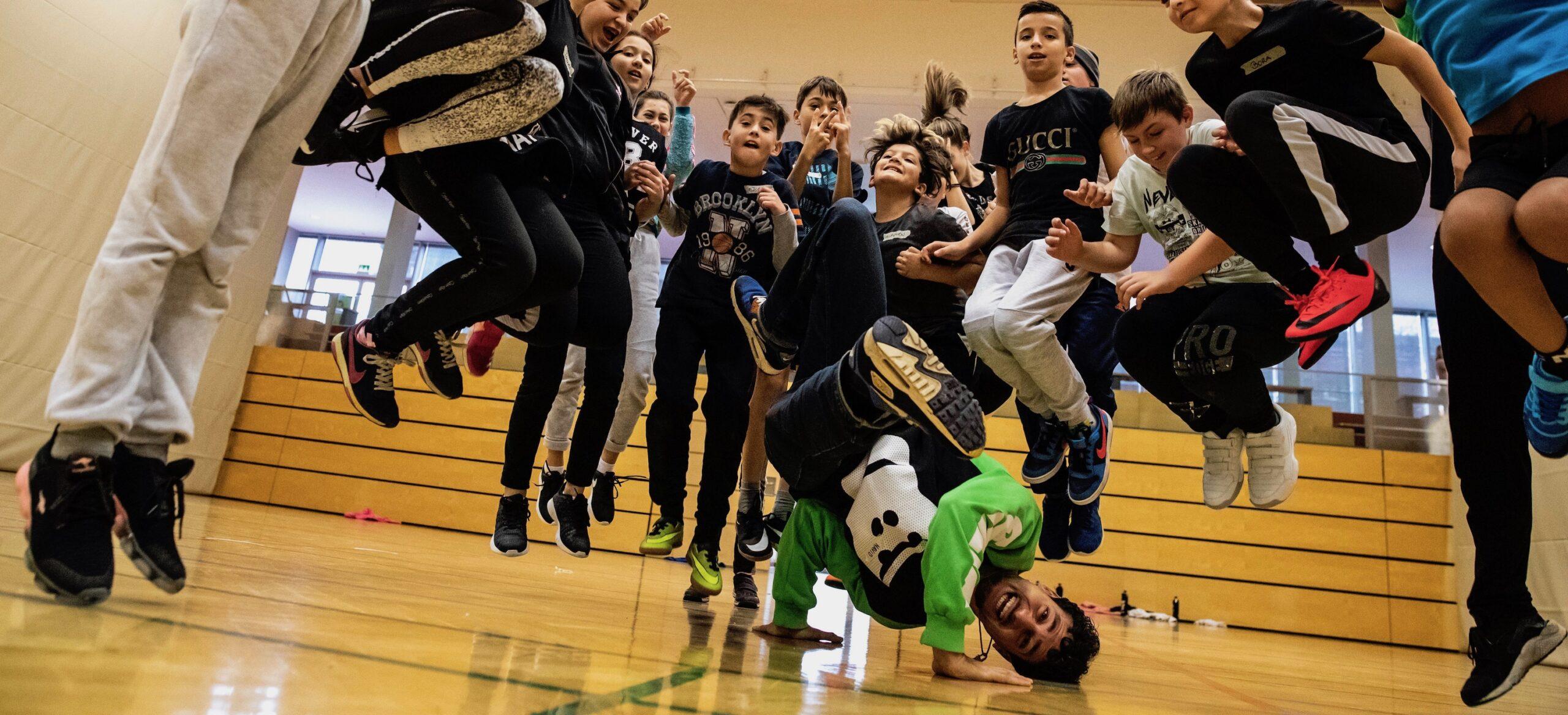 Breakdancer Moses macht einen Breakdance Trick in der Mitte von springenden Kindern.