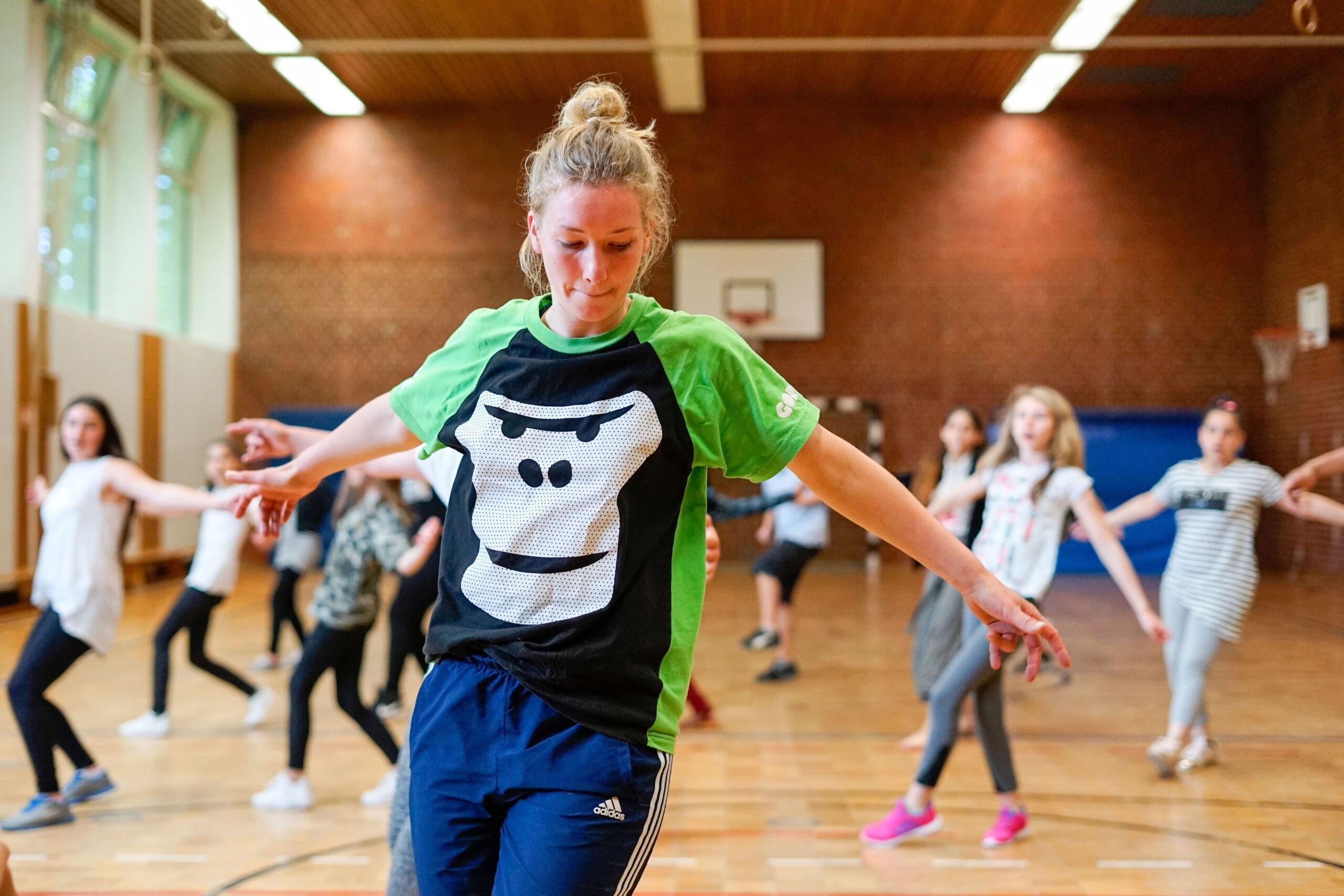 Eine GORILLA Botschafterin zeigt einer Gruppe von Schueler*innen in einer Turnhalle wie man Breakdancen lernt.