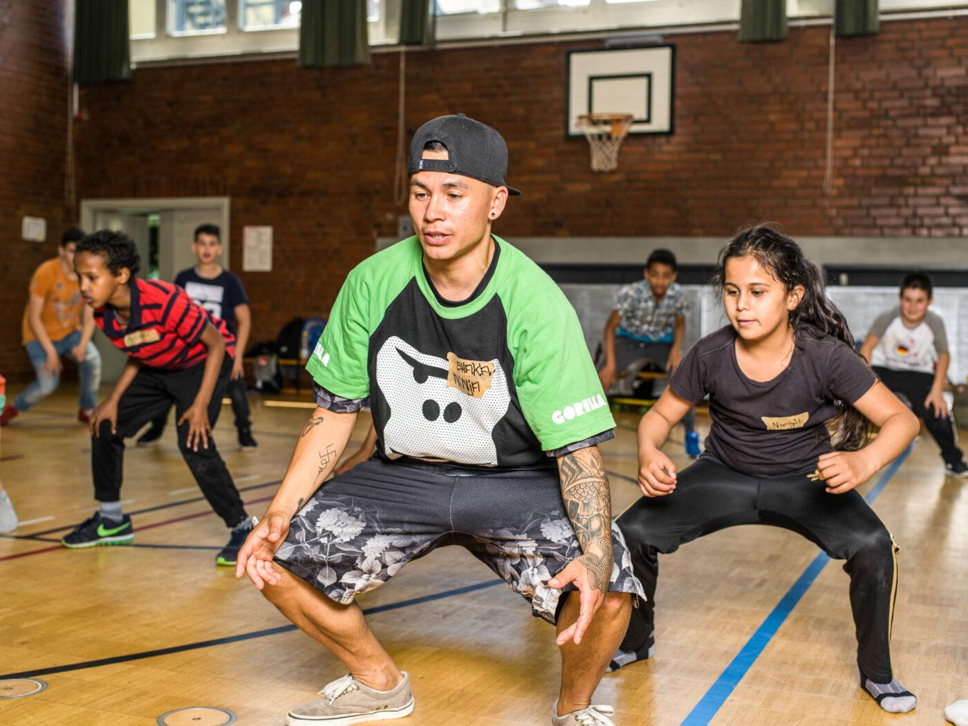 Ein GORILLA Botschafter zeigt einem Maedchen wie man Breakdancen kann im Rahmen eines GORILLA Workshops.