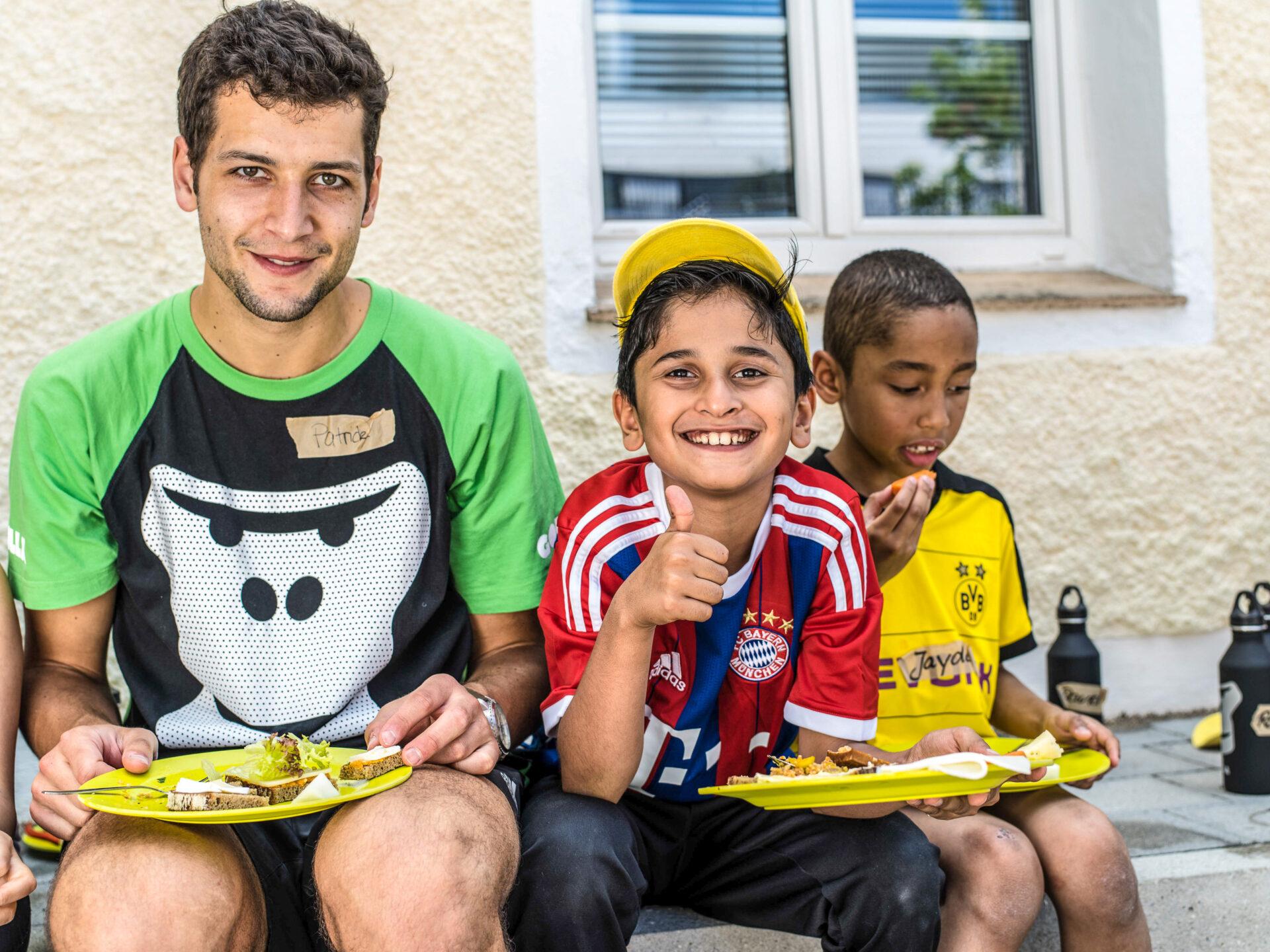 Ein GORILLA Botschafter und ein Kind essen voller Freude ihr Mittagessen im Rahmen eines GORILLA Workshops. Der Junge macht den Daumen hoch als Zeichen seiner Freude.