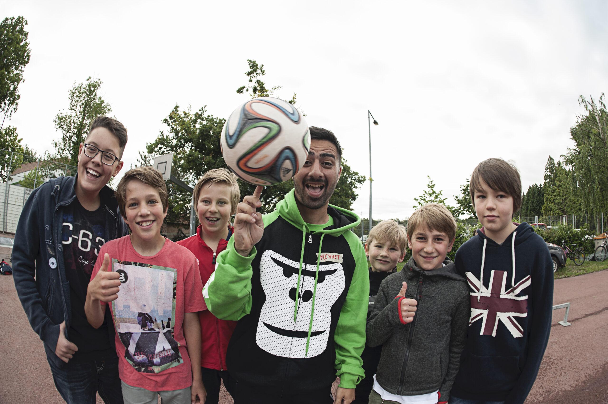 Eine Gruppe von Kids mit einem GORILLA Botschafter der einen Fußball auf dem Finger jongliert.