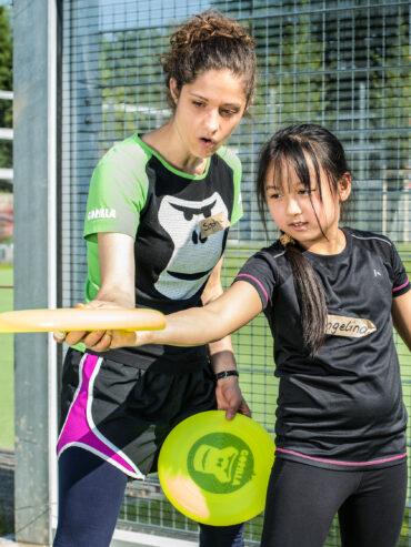 Eine GORILLA Botschafterin zeigt einem Maedchen wir man die Frisbeescheibe richtig haelt.