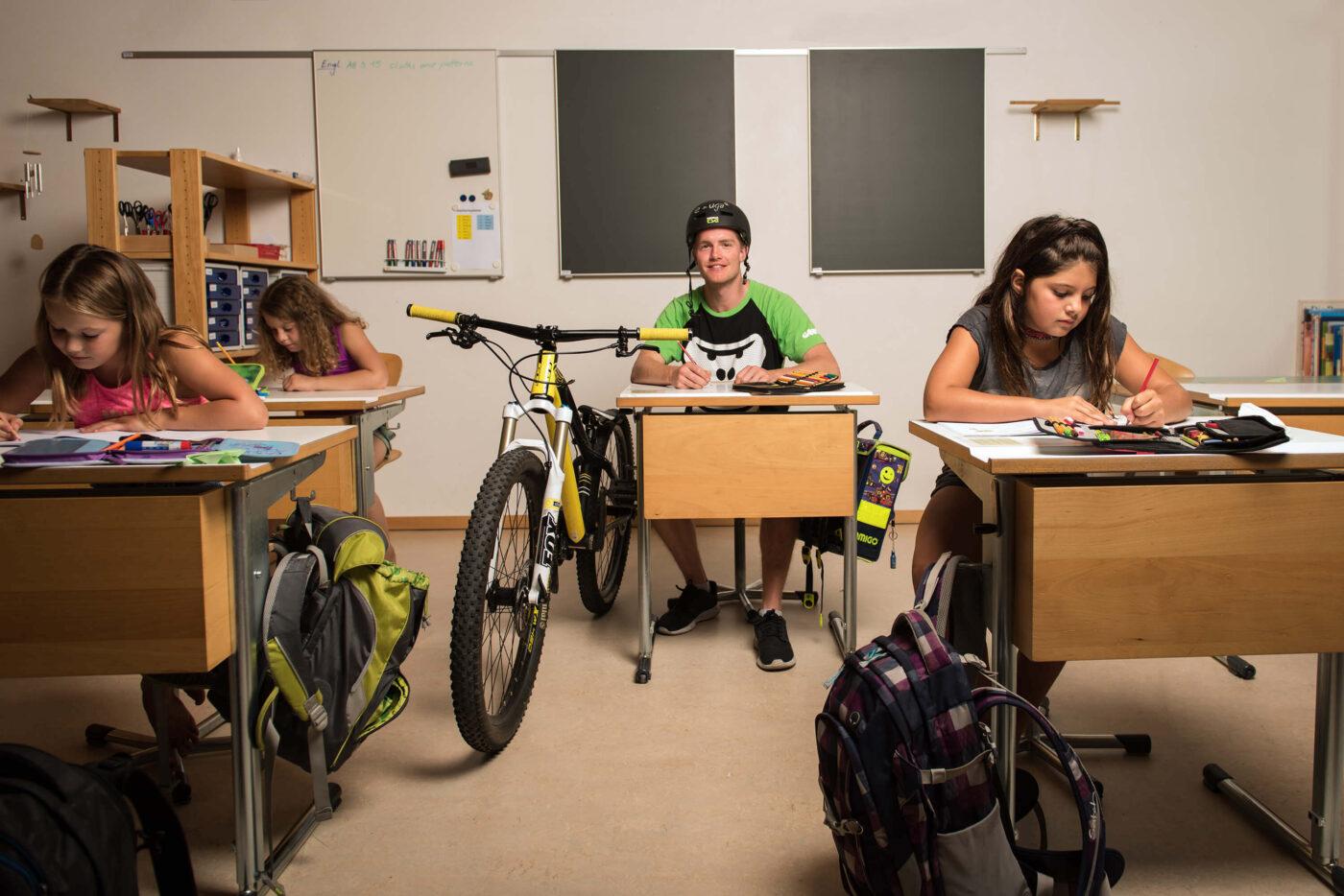 GORILLA Botschafter mit einem Bike sitzt in einem Schulzimmer mit 3 Maedchen.