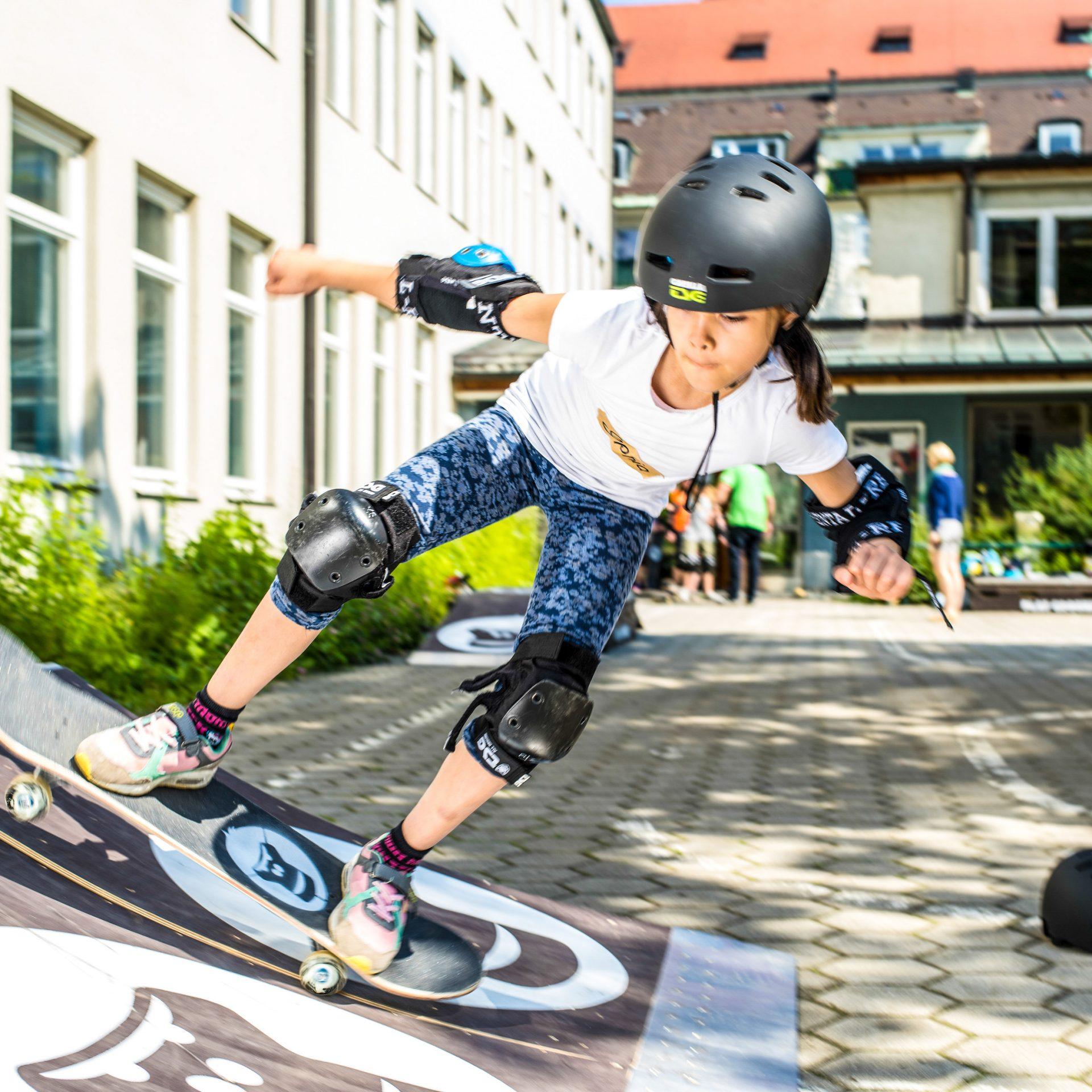 Ein Maedchen faehrt mit dem Skateboard die Anfahrt des GORILLA Playgrounds hoch.