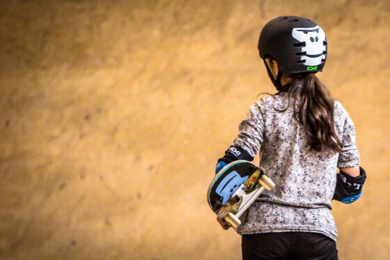 Ein Maedchen von hinten mit GORILLA Helm und Skateboard im Rahmen eines GORILLA Workshops in einem Skatepark.