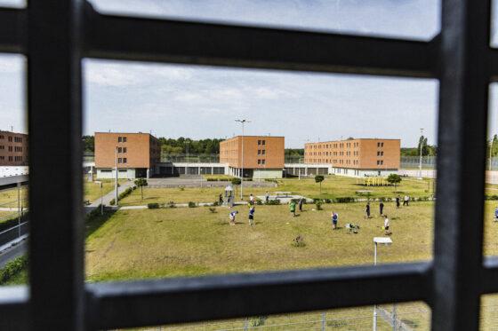 Blick aus einer Gefaengniszelle zum GORILLA Workshop der im Freien stattfindet.