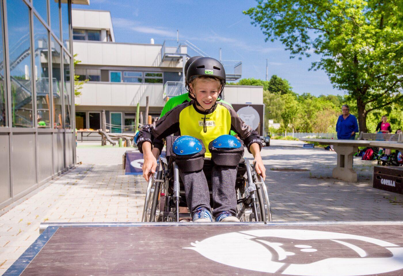 Ein Knabe rollt im Rahmen eines GORILLA Inklusionsworkshops mit dem Rollstuhl auf einen GORILLA Playground zu.