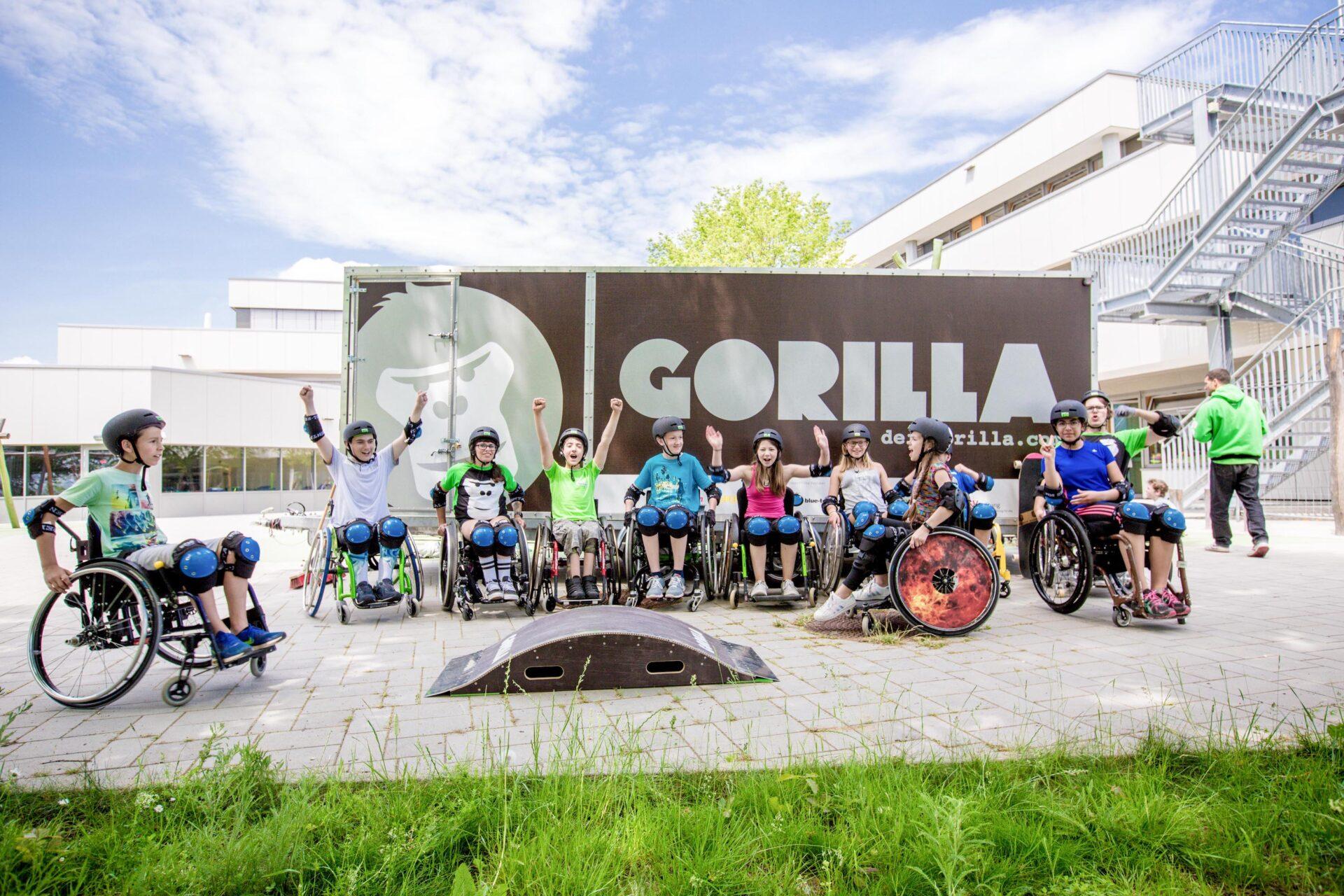 Gruppe von Kids im Rollstuhl reissen die Haende in die Hoehe im Rahmen eines GORILLA Workshops.
