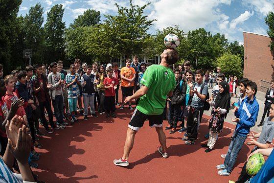GORILLA Botschafter macht in einem Kreis von begeisterten Kindern einen Trick indem er mit dem Kopf einen Fußball jongliert.