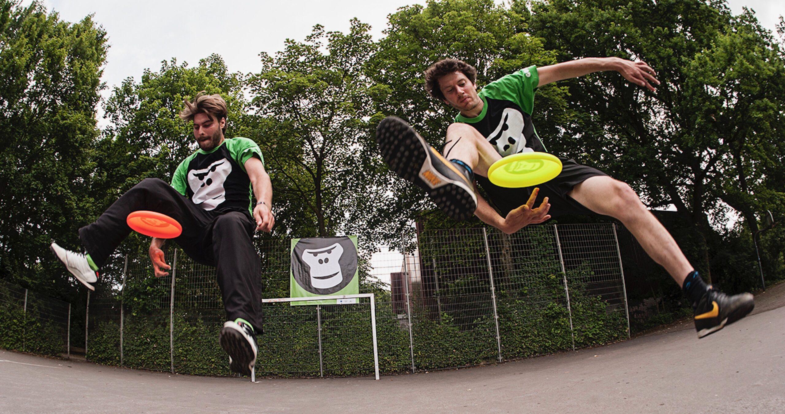 2 GORILLA Botschafter die am Frisbee spielen sind.