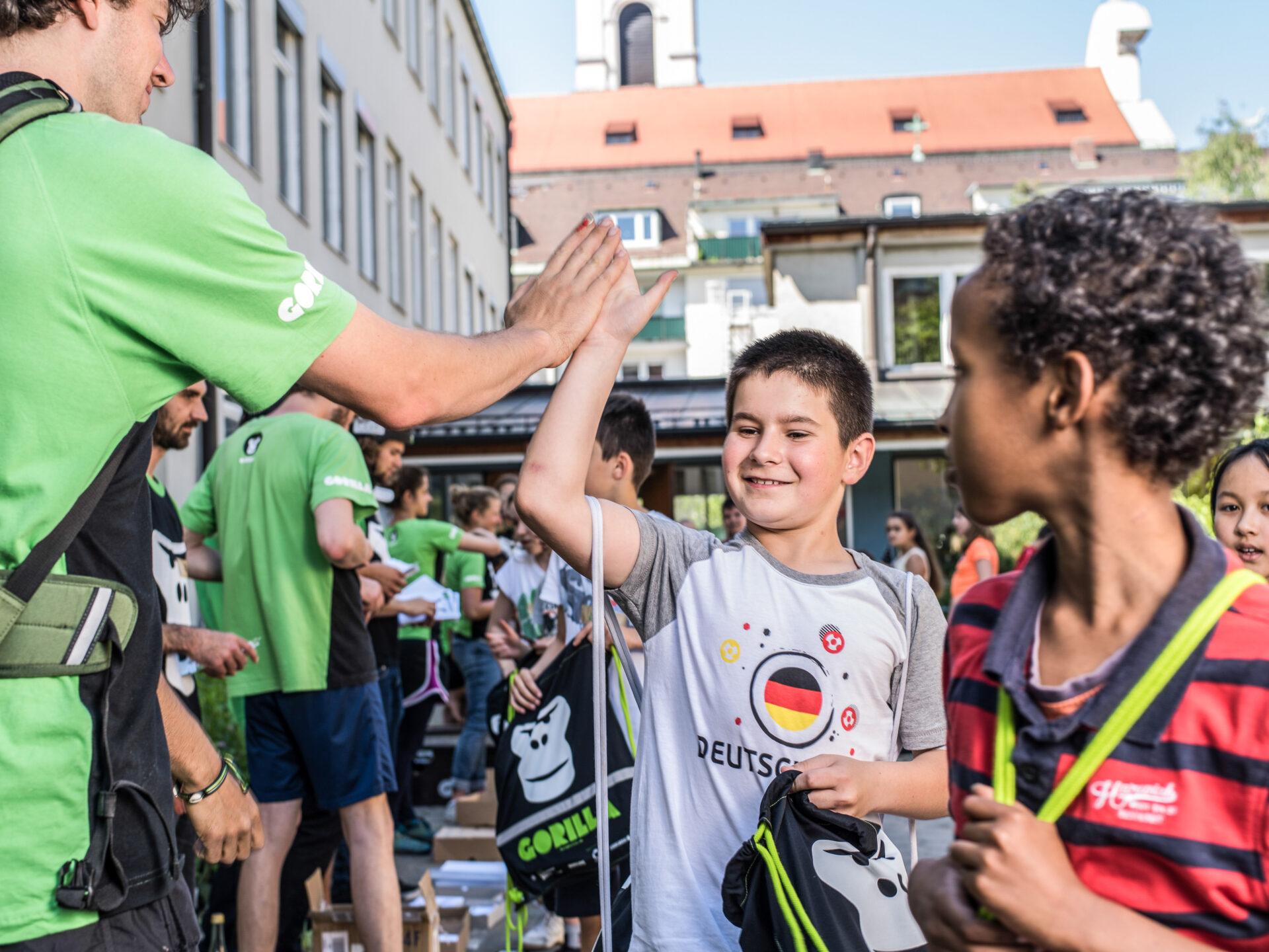 Ein GORILLA Botschafter und ein Junge klatschen sich zum Abschied eines GORILLA Workshops die Haende ab.