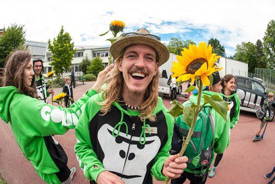 Ein GORILLA Botschafter haelt eine Sonnenblume in der Hand und lacht in die Kamera.